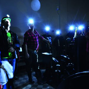 ludzie w kaskach z latarkami