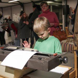 chłopczyk piszący na maszynie do pisania