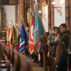 dzieci trzymające flagi w kościele
